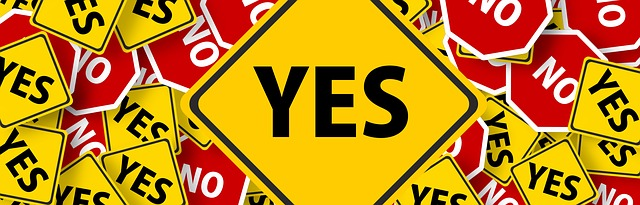 "A diamond-shaped yellow sign with the word ""yes"" is big in the center with lots of smaller yellow ""yes"" signs amidst red ""no"" signs."