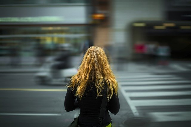 A picture of the back of a girl with blond hair and a blurry city street in front of her to represent Acts 18:10 in which God tells Paul He has many people in the city.