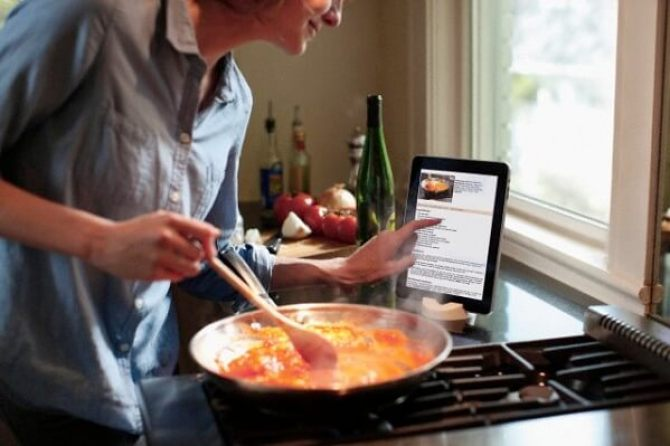Person cooking and interacting with a recipe displayed on a tablet --- Image by © Ron Royals/Corbis