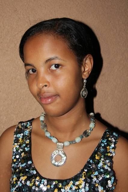 Sakina, Sidi's daughter models a mother of pearl and sterling silver necklace.
