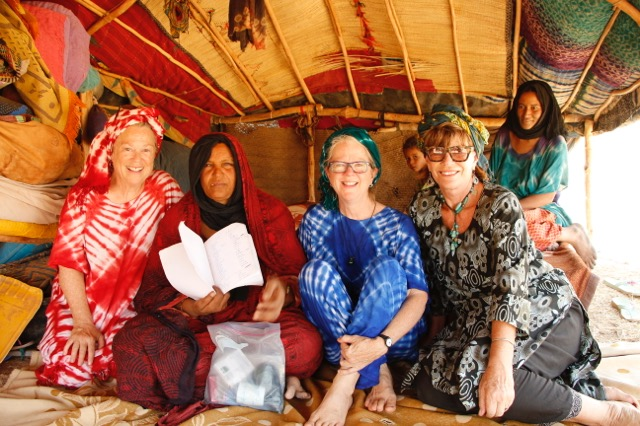 Pat Manzon, Tinzere, Dr. Becky, Leslie Clark in the tent of Tinzere at Tchinwezizil showing her record of births and complications. Although Tinzere herself can neither read nor write, she recognizes the importance of record-keeping and was assisted by others in her community