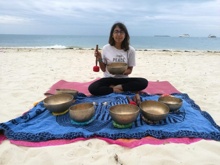 Nomad girl sitting on the beach surrounded by bronze bowls