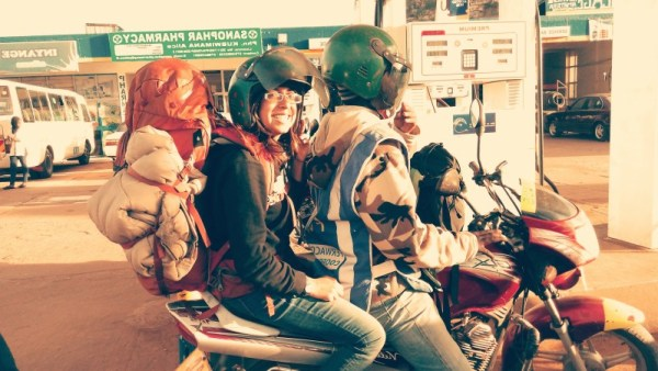 Solo female backpacker on  on the back of a motorbike with a big red backpack