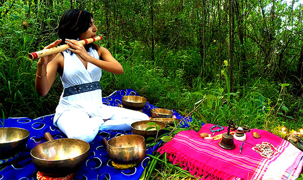 Sound healer in forest with bansuri flute