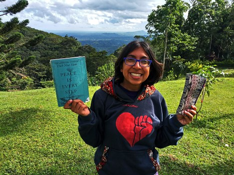 Narissa smiling and holding with Peace is Every Step book by Zen master Thich Nhat Hanh and the purple case from my Plum Village nun friend