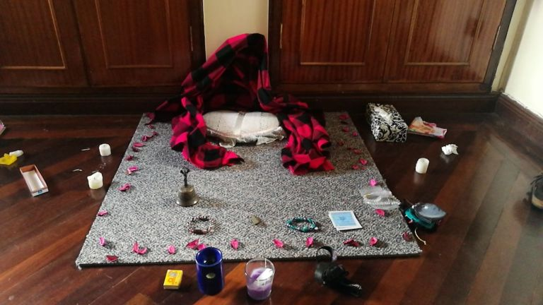 square grey mat with a small meditation cushion on it and a pink blanket, surrounded by candles and flower petals