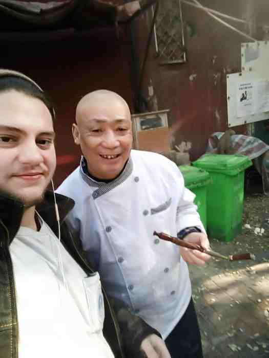 Me standing with an old chinese man smoking a weird cigar pipe like thing in an alley in Beijing