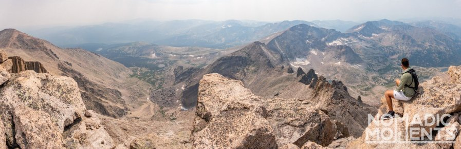 A hiker sits on a boulder overlooking the Rocky Mountain landscape.