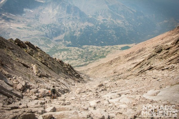 A hiker descends a rocky path overlooking a valley far below.