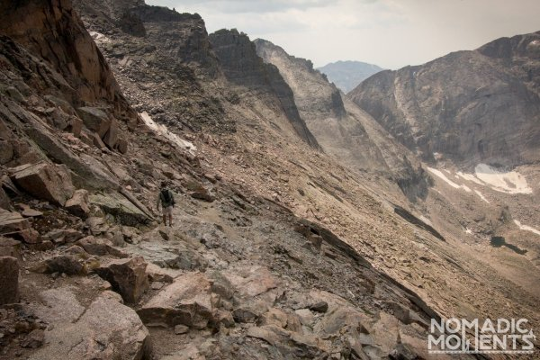 A hiker traverses a rocky ledge in Rocky Mountain National Park.