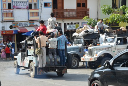 People hanging off the back of a jeep in Belén de Umbría, Risaralda, Colombia