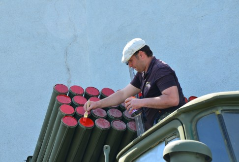 A man painting a military vehicle at the National Museum of the History of Ukraine in the Second World War Memorial Complex in Kiev, Ukraine