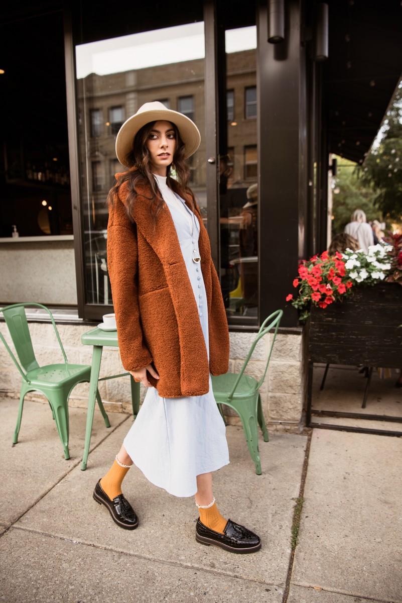 Penelope Bauer walking in Logan Swuare Chicago wearing hat sherpa jacket mustard socks and loafers