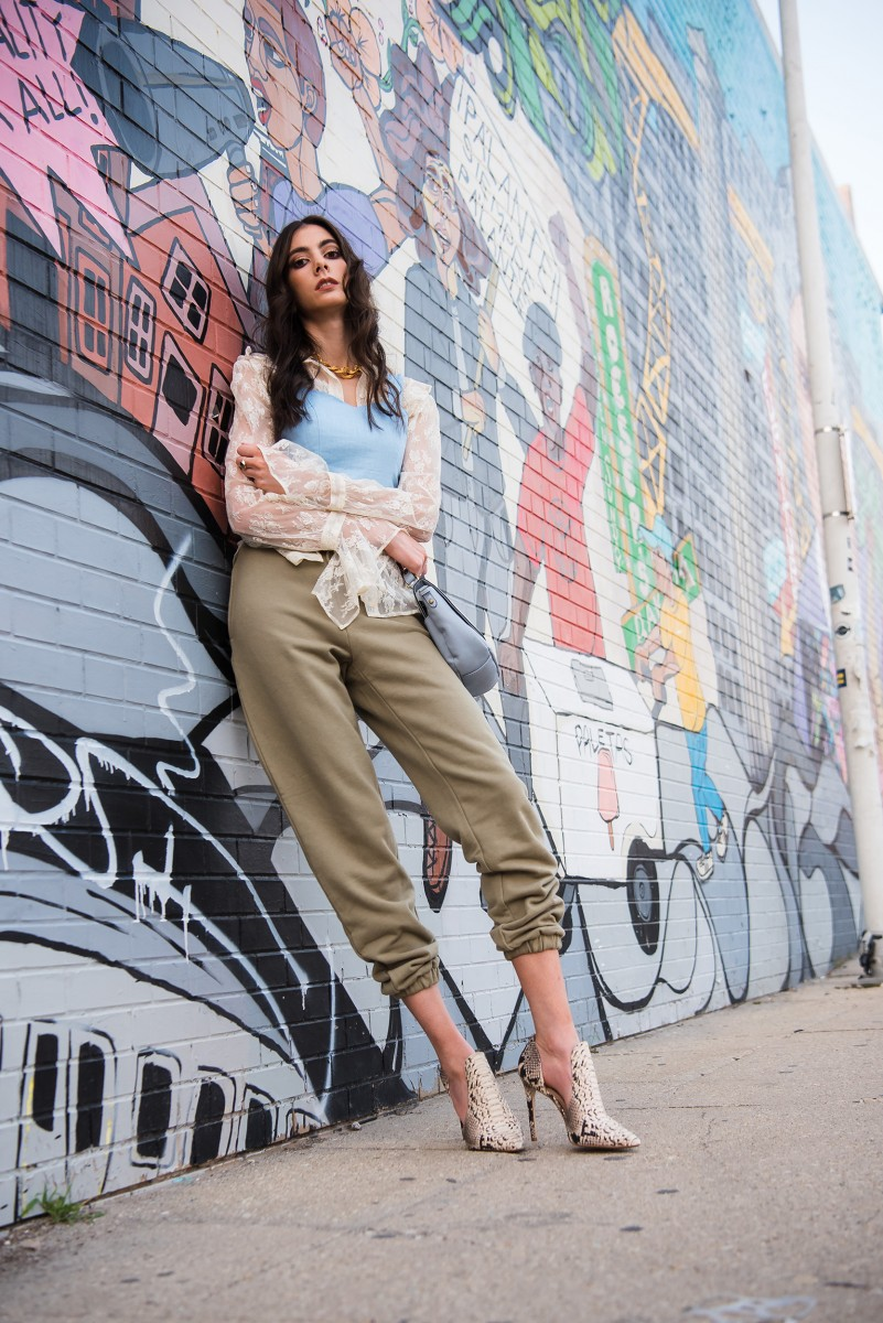 Penelope Bauer wearing sweatpants lace blouse overlay shirt snake skin heels
