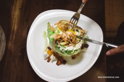 The Wedge Salad  Bacon   Tomatoes   Cucumber   Blue Cheese   Egg Crispy Onions   Green Goddess dressing  This salad features a perfectly poached egg cooked at 63°