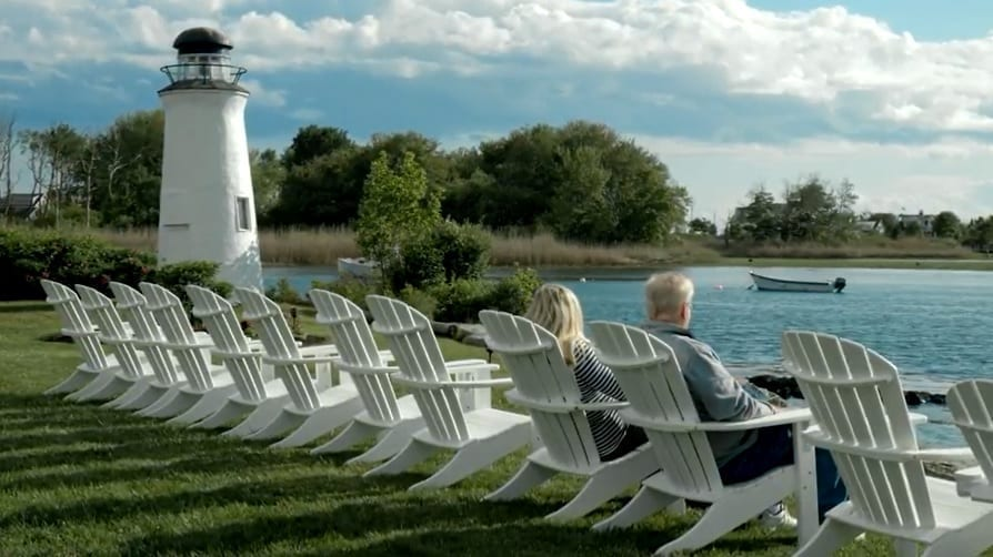 Couple in riverside Adirondack chairs next to a lighthouse.