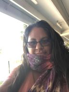 A woman seated, looking at the camera, beside a window with light streaming in. She has long dark hair, black glasses, a pastel purple and yellow scarf and pink T-shirt.