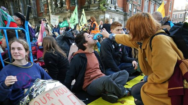 A protester, who has glued himself to the ground at Millbank near to the junction with Great College Street, receives refreshment during an Extinction Rebellion (XR) protest in Westminster, London.