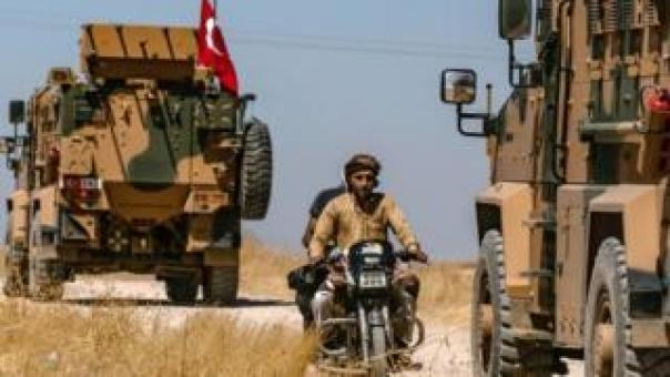 Turkish military vehicles drive on a patrol in the Syrian village of al-Hashisha on the outskirts of Tal Abyad