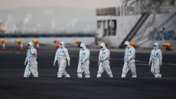 TOPSHOT - People wearing protective suits walk from the Diamond Princess cruise ship, with around 3,600 people quarantined onboard due to fears of the new coronavirus, at the Daikoku Pier Cruise Terminal in Yokohama port on February 10, 2020. - Around 60 more people on board the quarantined Diamond Princess cruise ship moored off Japan have been diagnosed with novel coronavirus, the country's national broadcaster said on February 10, raising the number of infected passengers and crew to around 130. (Photo by CHARLY TRIBALLEAU / AFP) (Photo by CHARLY TRIBALLEAU/AFP via Getty Images)
