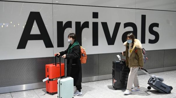 """Passengers wear face masks as the push their luggage after arriving from a flight at Terminal 5 of London Heathrow Airport in west London on January 28, 2020. - Chinese President Xi Jinping said Tuesday the country was waging a serious fight against the """"demon"""" coronavirus outbreak and pledged transparency in the government's efforts to contain the disease. (Photo by DANIEL LEAL-OLIVAS / AFP) (Photo by DANIEL LEAL-OLIVAS/AFP via Getty Images)"""