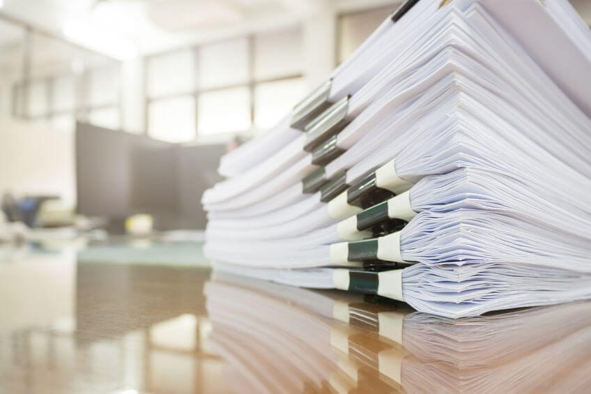 stack of papers in binder-clips