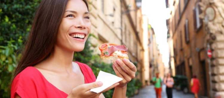 Pizza woman eating pizza slice in Rome, Italy smiling happy outd
