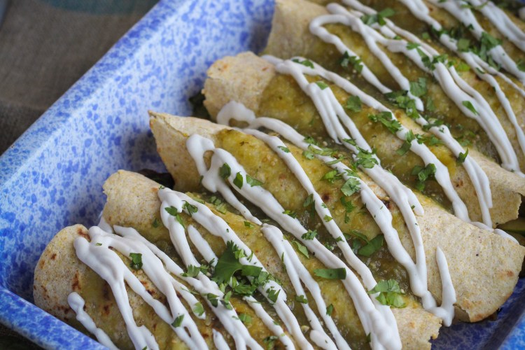 Vegan Enchiladas Verdes with Potato and Black Bean Filling after cooking, topped with Cashew Sour Cream and Cilantro