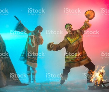The beautiful young woman and young man with appearance of Siberian indigenous people are dressed in ethnic clothing.  The blonde young woman and attractive man are dancing a folk dance. The man is drumming in shaman drum. Theatrical performance in ethnic decoration, studio shooting in smoke