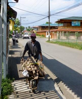 man hauling wood through Cahuita,Costa Rica
