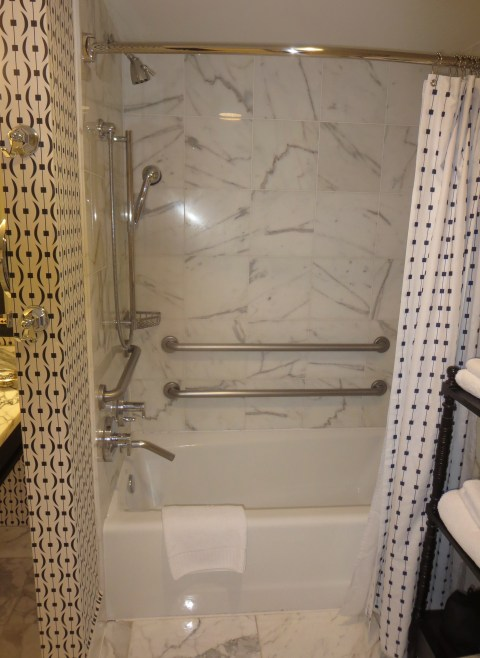 Shower over tub full of handrails. The curtain blows in the wind.