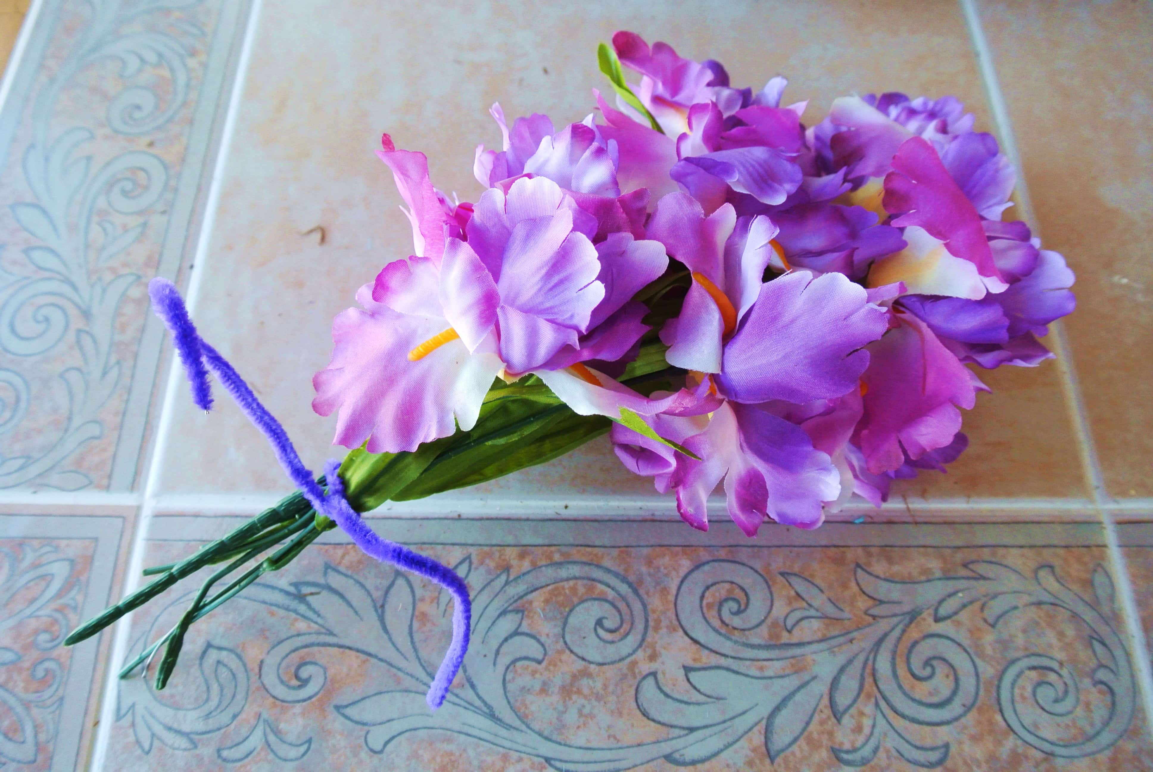 Tie ends of faux purple flowers tightly with a pipe cleaner