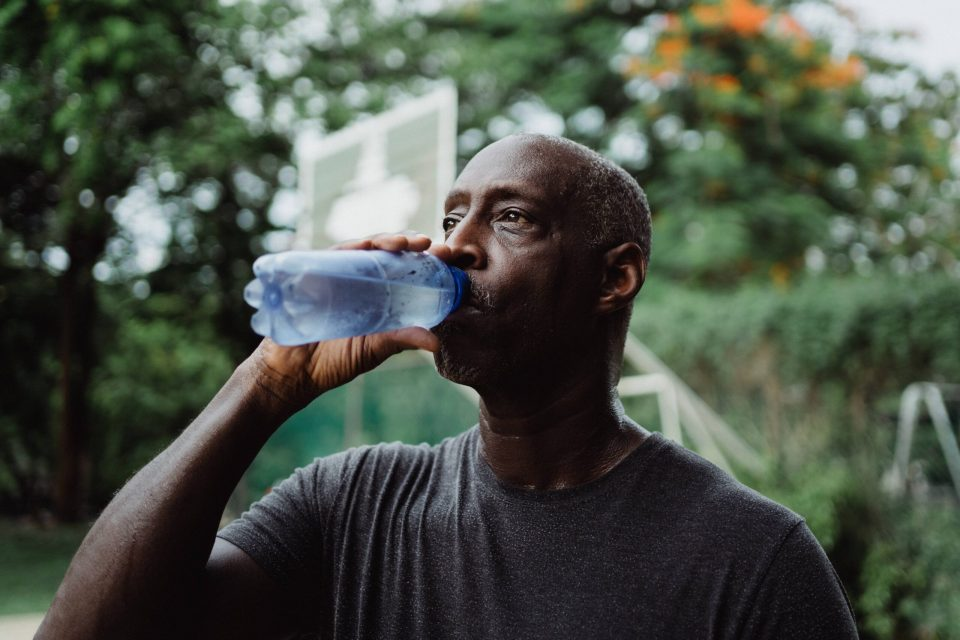 humans drinking water from plastic bottle