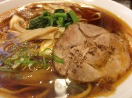 The Tsumugi ramen is topped with a slice of pork, scallions, Japanese leaks, bamboo shoots, and a green leafy vegetable