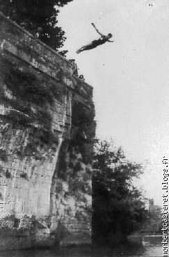 Man diving from a rocky outcrop into a river