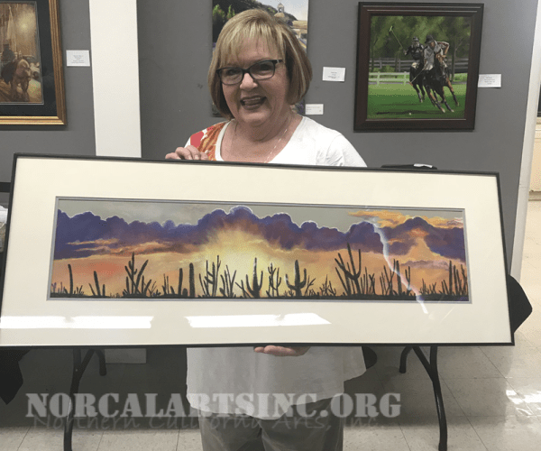 Sally Durante poses with her pastel painting of a desert sunset.