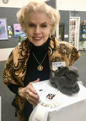 Marilynn Fairchild poses with one of her award-winning sculptures, a rabbit