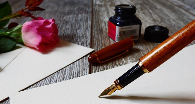 Photo of fountain pen and withe stationery on a rustic wooden desk with a pinnk rose and black ink bottle.