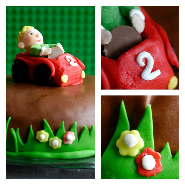 An edible car made of sugar paste with liquorice wheels and a steering wheel made of milk chocolate