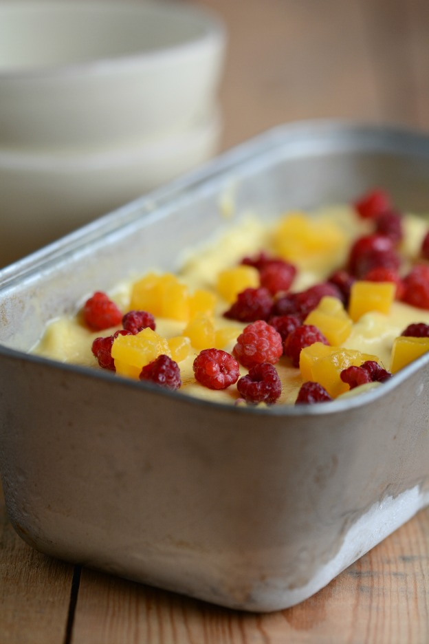 Mango ice cream topped with frozen mango cubes and wild raspberries