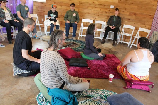 A group meditating crosslegged on the floot