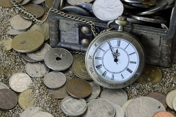 a pocket watch, treasure chest and many coins
