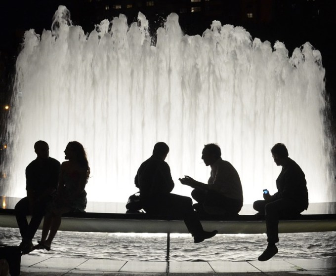 People talking sitting around a fountain at night