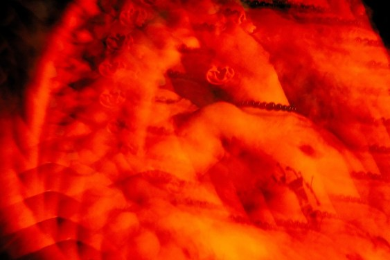 Psychedelic photo in red of a shirtless person leaning backward and smiling