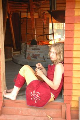 person in red costume sitting in a doorway