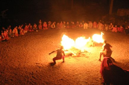 People in a large circle with people in the center wielding fire