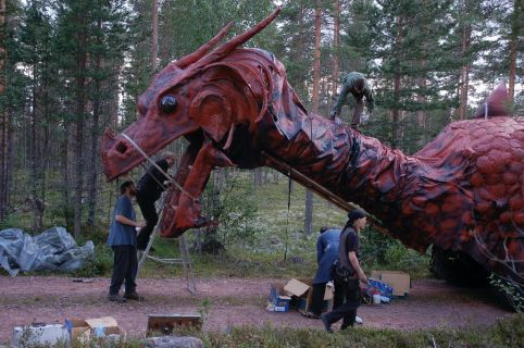 People working on a large animatronic dragon in the woods