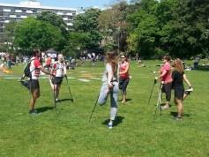 Petit groupe de 6 personnes effectuant des étirements (quadriceps) après une séance de marche nordique dans la Parc Montsouris à Paris.