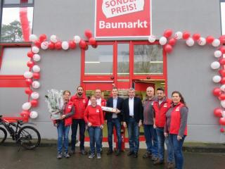 Ortsbürgermeister Werner Hartke (4. v. r.) und Jonas Berger von der Wirtschaftsförderung (5. v. r.) überreichten Filialleitung Bianca Peesel (1. v. l.) und Bezirksleiter Dieter Marx (4. v. l.) zusammen mit dem ganzen Team ein präsent zur Neueröffnung. Foto: Stadt Lingen