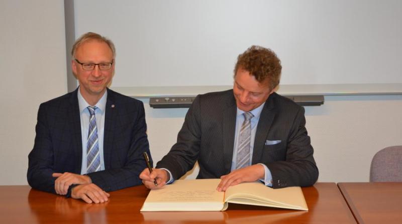 """Bürgermeister Helmut Höke gemeinsam mit Jens Beeck beim Eintrag in das """"Goldene Buch"""" der Gemeinde Geeste. Foto: Gemeinde Geeste"""